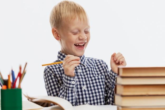 Een lachende schooljongen zit aan een tafel met schoolboeken en maakt huiswerk. terug naar school. witte achtergrond.