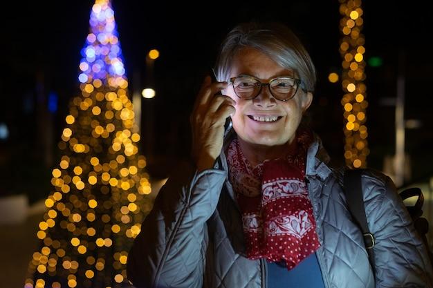 Een lachende senior dame praten op de mobiele telefoon. buiten in de nacht met een kerstboom achter haar. gele lichten decoraties.
