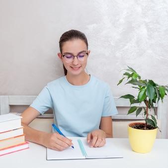 Een lachende tienerstudent die aan een tafel met boeken zit, schrijft een opdracht in een notitieboekje. het meisje is een student die studeert voor toelating tot de universiteit, middelbare school. terug naar schoolconcept.