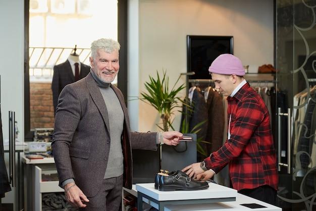 Een lachende volwassen man met grijs haar en een sportieve lichaamsbouw houdt een creditcard vast in een kledingwinkel. een mannelijke klant met een baard en een winkelbediende in een boetiek.