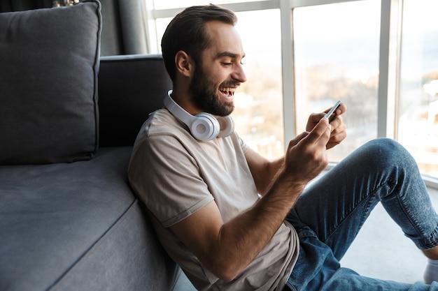 Een lachende vrolijke jongeman binnenshuis thuis spelletjes spelen met de mobiele telefoon op de vloer zitten.
