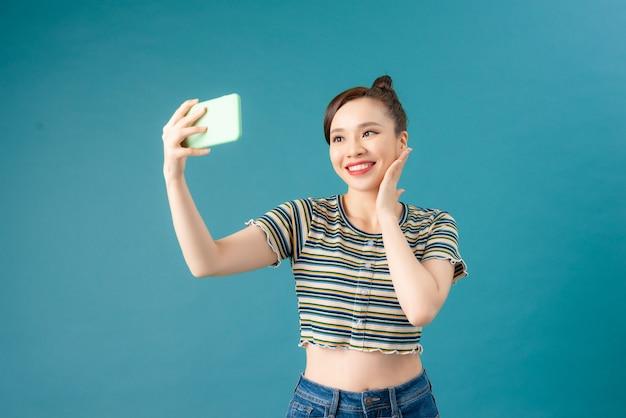 Een lachende vrouw die een selfie-foto maakt op een smartphone