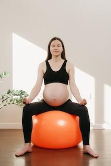 Een lachende zwangere vrouw zit op een oranje oefenbal en ontspant na een fitnesstraining met haar armen op haar knieën thuis. gezonde fit zwangerschap.