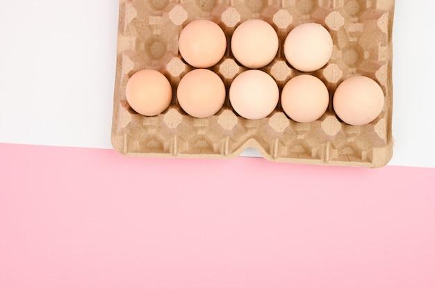 Een lade van eieren op een witte en roze achtergrond. eco dienblad met testikels. minimalistische trend, bovenaanzicht. eiertray. pasen concept.