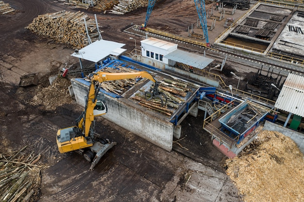 Een lader laadt houtblokken van bovenaf vanuit een drone in een houtverwerkingsfabriek