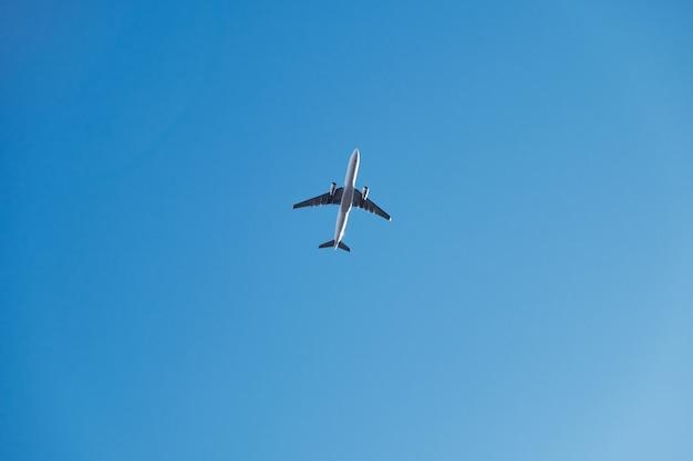 Een lage hoek die van een vliegtuig is ontsproten dat onder een blauwe hemel en zonlicht vliegt