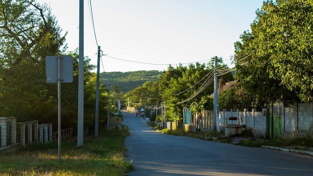 Een landelijke lege straat in een dorp, paaltjes en hekken langs de weg, veel groen, varul cel mic, moldavië