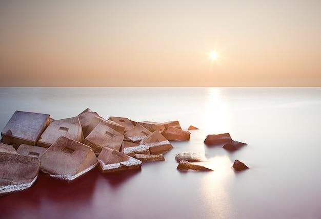 Een lange blootstelling van rotsformaties in de zee bij zonsondergang