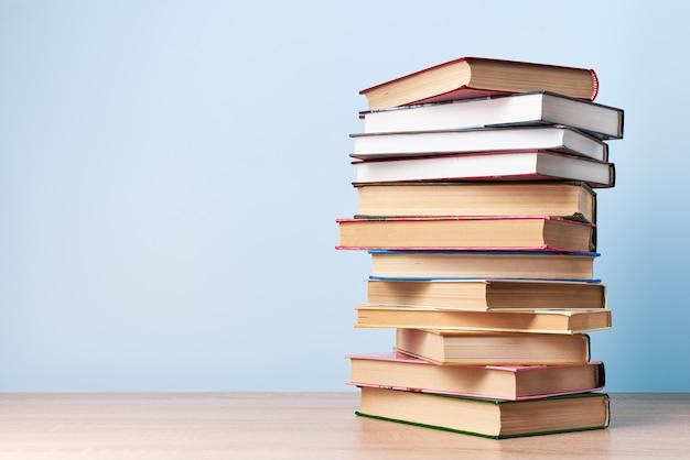 Een lange, chaotische stapel boeken staat op een houten tafel tegen een lichtblauwe muur