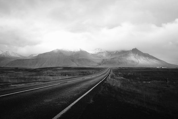 Een lange door de woestijn met bewolkte heuvels in de verte