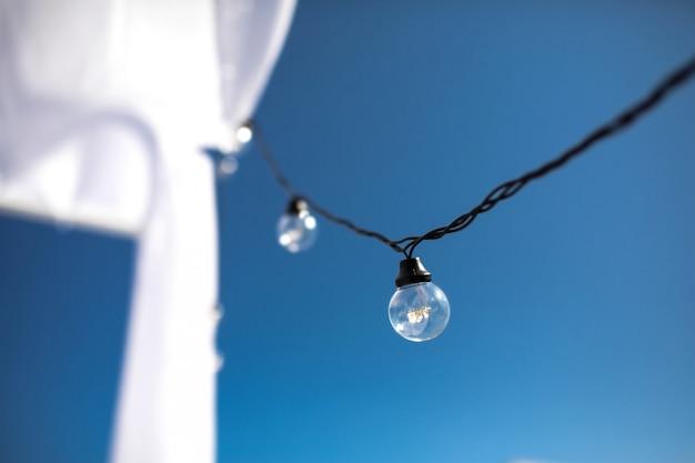 Een lange elektrische slinger voor verlichting met witte gloeilampen