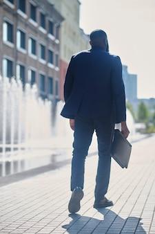 Een lange man met een donkere huidskleur in een pak op straat