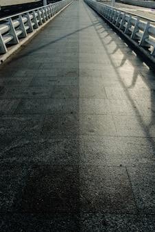 Een lange marmeren tegelweg met witmetalen relingen met een verdwijnende lijn aan de horizon