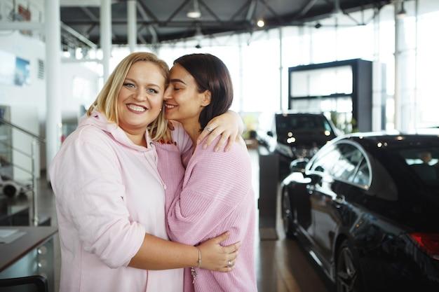Een lange mooie vrouw en een dikke blonde vrouw bij een dealer kochten een auto. het concept van het kopen van een voertuig.