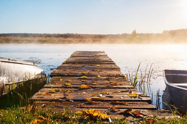 Een lange pier die leidt naar de rivier, herfstbladeren liggen op de taart