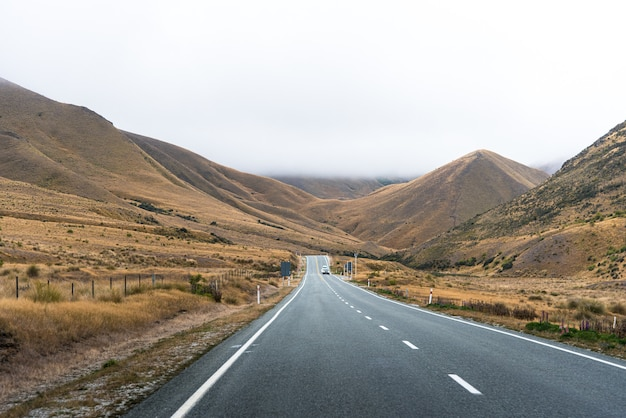 Een lange rechte weg met wolken en bergen in de avond