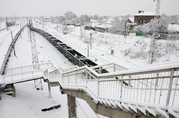 Een lange trein van goederenwagons beweegt zich langs de spoorlijn. spoorweglandschap in de winter na sneeuwval
