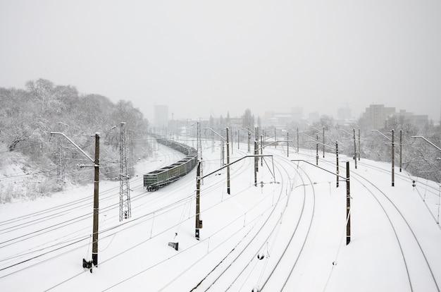 Een lange trein van goederenwagons beweegt zich langs de spoorlijn.