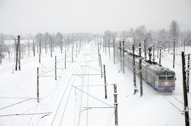 Een lange trein van personenauto's rijdt over het spoor. spoorweglandschap in de winter na sneeuwval