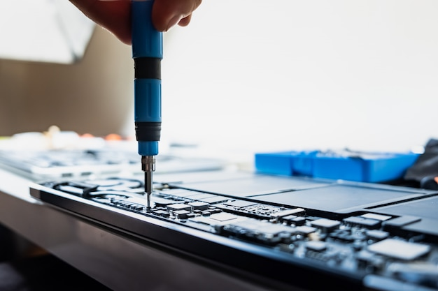 Een laptop demonteren bij een professionele service. persoon voert regelmatig onderhoud uit en schroeft delen van een moderne draagbare computer los