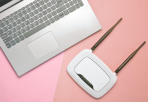 Een laptop en een wifi-router op een gekleurd papier oppervlak