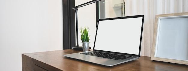 Een laptop met een witte lege schermcomputer zet op een houten tafel in een comfortabele kamer.