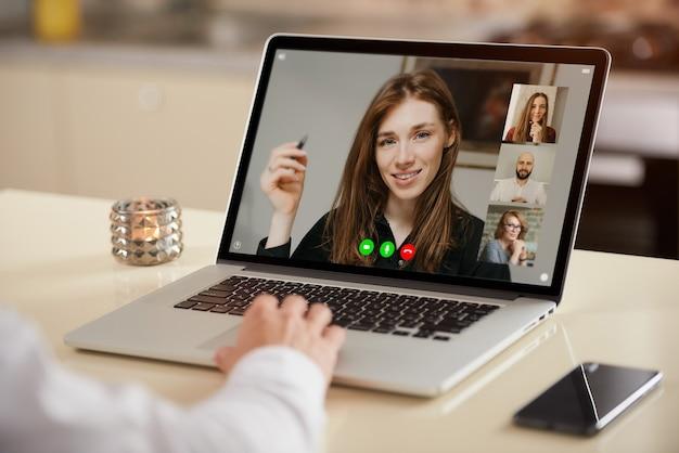 Een laptopweergave van de telecommunicatietoepassing tijdens een online vergadering over de schouder van een man.