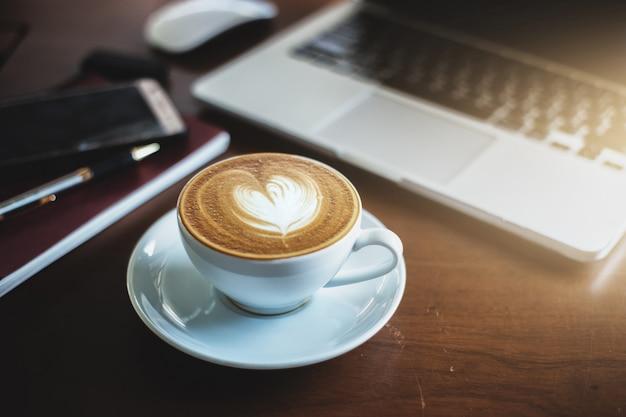 Een latte koffie en laptop op de tafel.