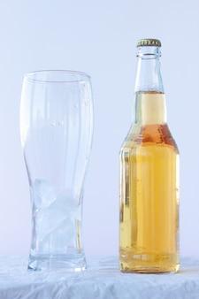 Een leeg bierglas met ijs staat op een witte achtergrond naast een volle fles bier.