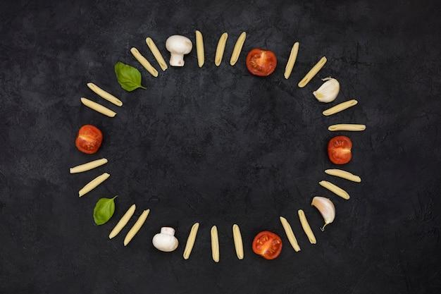 Een leeg cirkelvormig kader gevormd met ongekookte garganelli-pasta; tomaten; paddestoel; teentje knoflook en basilicum op zwarte gestructureerde achtergrond