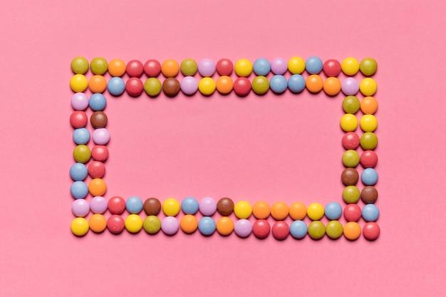 Een leeg frame gemaakt met kleurrijke gem snoepjes op roze achtergrond