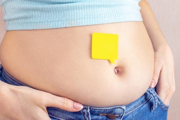 Een leeg geel papier blanco bericht op buikvet met handen knijpt in de taille van een jonge vrouw in spijkerbroek.