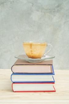 Een leeg kopje koffie en een stapel boeken.