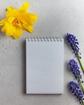 Een leeg notitieblok met paarse en gele bloemen