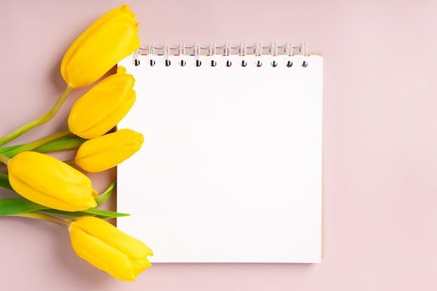Een leeg notitieblok om op te schrijven en gele tulpen op een roze achtergrond. de lentesamenstelling met bloemen