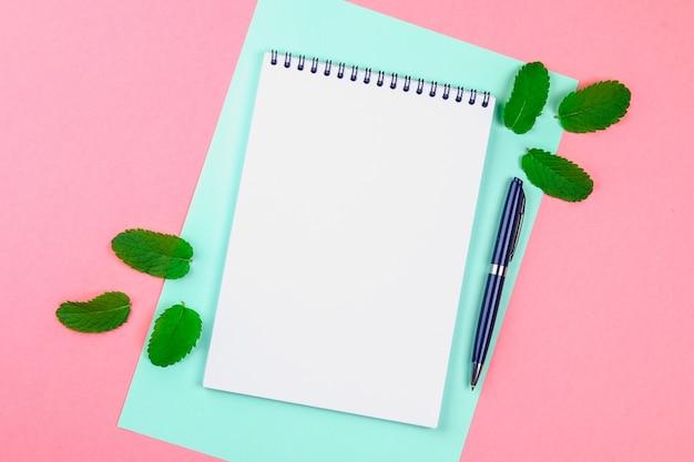 Een leeg notitieboekje met een handvat en muntblaadjes op roze pastelkleurachtergrond. mock-up, lijst,