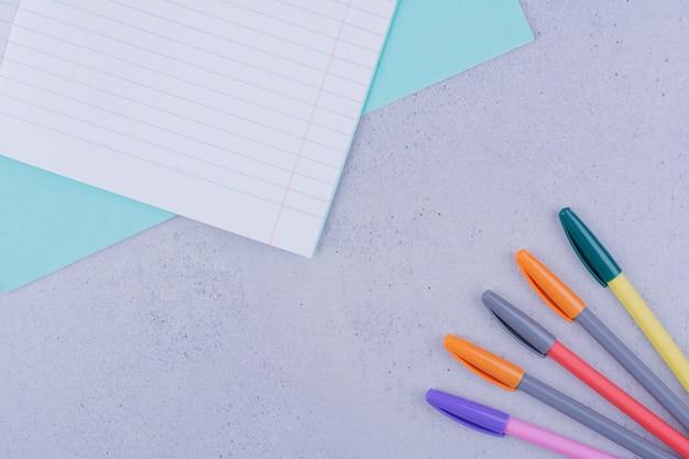 Een leeg notitieboekje met rond kleurpotloden op grijs oppervlak