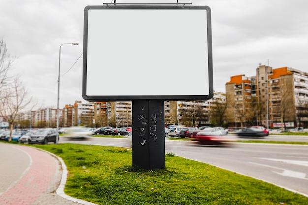 Een leeg reclamebord in het midden van de stadsweg