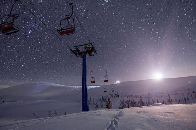 Een leeg skigebied met kabelbanen gelegen op winterheuvels