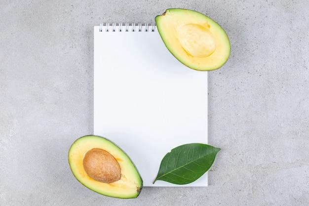 Een leeg vel papier met gesneden avocado. hoge kwaliteit foto