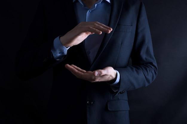 Een leeg werkstuk. een zakenman in een pak op een zwarte achtergrond houdt zijn handen beschermend gebaar