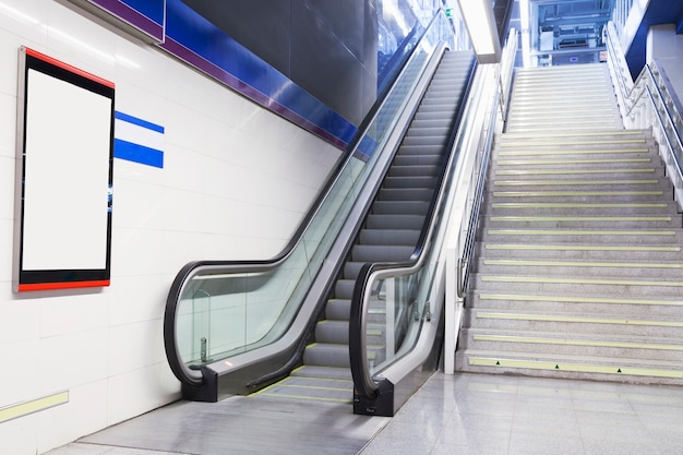 Een leeg wit aanplakbord op muur dichtbij de roltrap en de trap
