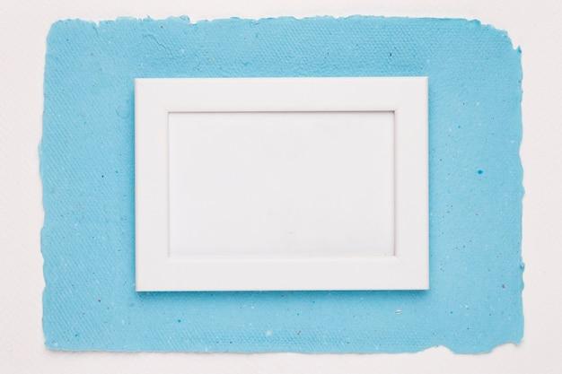 Een leeg wit grenskader op blauw papier over witte achtergrond