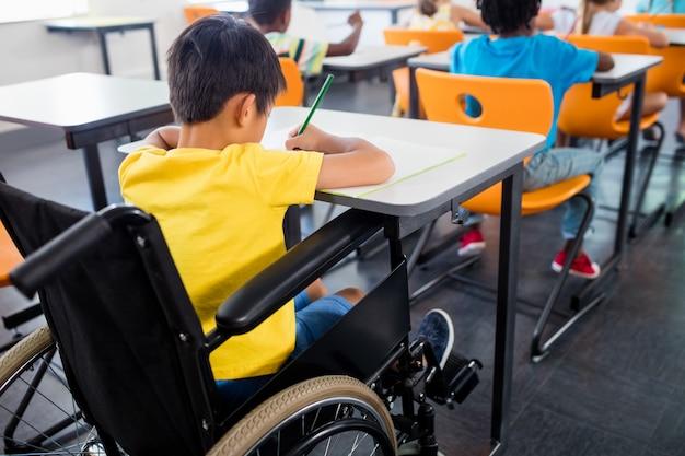 Een leerling als rolstoel die bij zijn bureau werkt