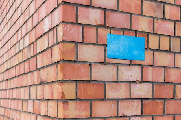 Een lege blauwe plaat is op een bakstenen muur geschroefd. een bord op de hoek van een bakstenen gebouw.