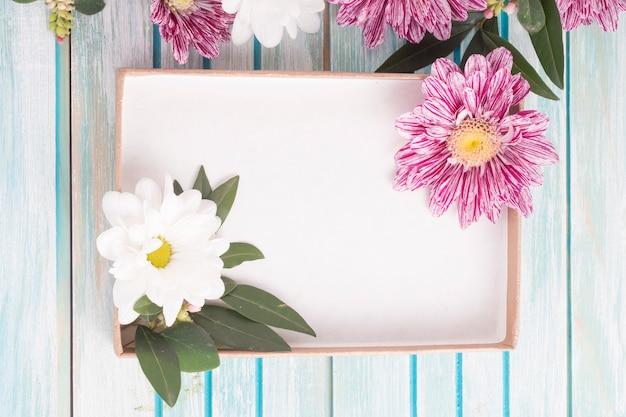 Een lege doos met madeliefje en chrysanthemum bloemen