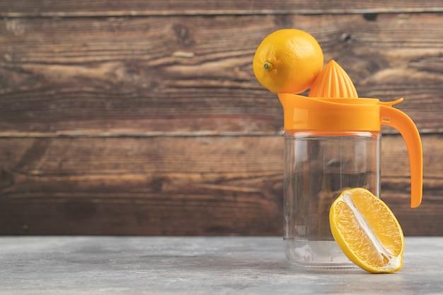 Een lege glazen werper met een hele citroen op een houten.
