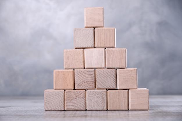 Een lege houten kubus op de tafel.