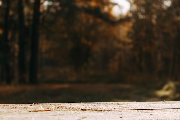 Een lege houten tafel en een ongericht herfstbos op de achtergrond. geweldig voor het monteren van productdisplays.