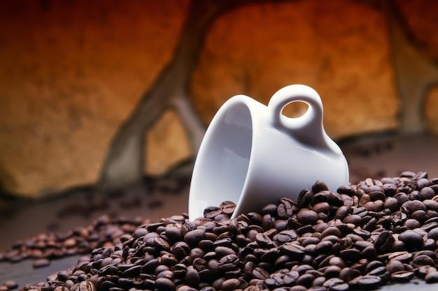 Een lege kop geplaatst tussen koffiebonen.